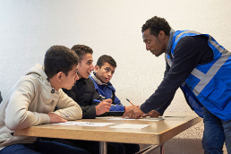 Three teenage boys sit at desk and receive instruction from an educator.